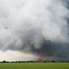 Two dusty tornadoes dance across open fields beneath a a large wall cloud near Crowell, TX, on April 23, 2021.