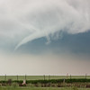 A whispy funnel cloud looms behind a cemetery near Hitchcock, OK, on May 19, 2010.