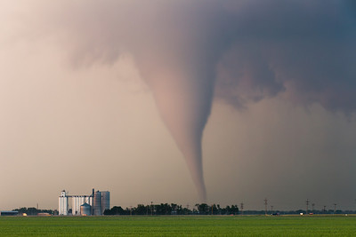 A classic cone tornado near Sanford, KS, takes on brilliant hues as the sun sets on May 18, 2013.
