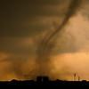A rare anticyclonic (clockwise-rotating) tornado kicks up dust and debris shortly before striking a municipal airport near El Reno, OK, on April 24, 2006.
