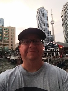 Shortly after arriving in Toronto, I took a walk along the lakefront before heading to dinner. Behind me is the CN Tower. The red building is a pastry shop called BeaverTails. Cell phone photo.