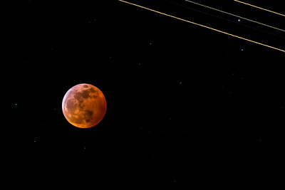Lunar Eclipse: An airplane flies through the camera field in the upper right corner at the time of peak totality