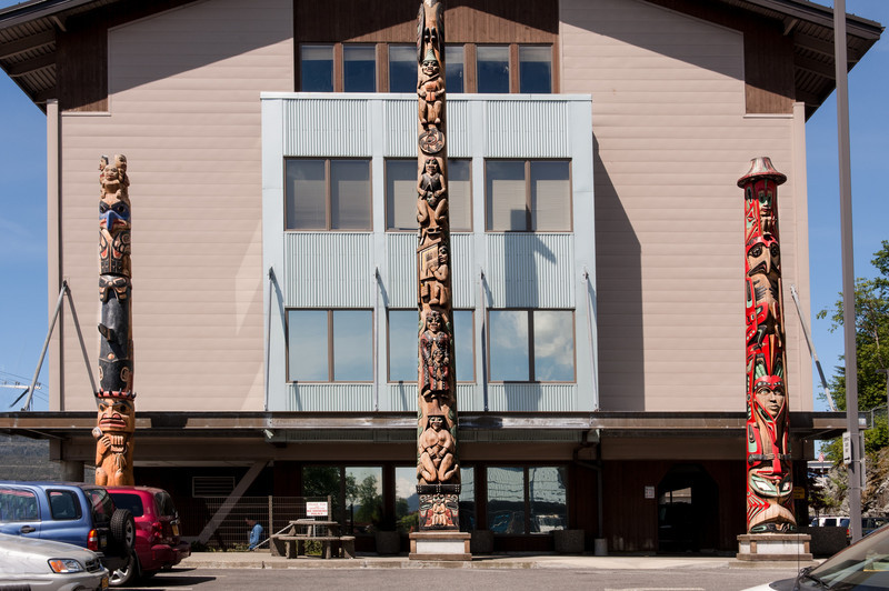 Three poles located outside the Ketchikan Indian Community Center Building.