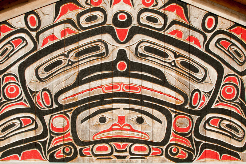 Interior wall carving in Potlach Park near Ketchikan.  This magnificent carving is about 10 feet tall, is located in a longhouse and was carved by Brita Alander, a female Haida Native American of the Eagle Clan.  Potlach Park is a relatively new totem park.  Brita carved many (most?) of the totems and other artwork at Potlach Park.