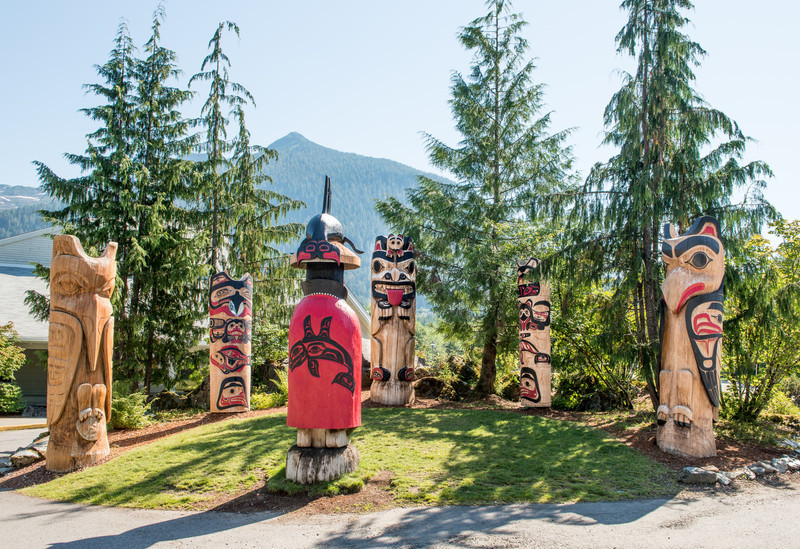 """These 6 totem figures are known as the """"Council of Clans.""""  They are located near the main entrance to the Cape Fox Lodge in Kethchikan.               The figure wearing a red button blanket is holding a staff known as the Naa Kaani pole (not visible in this photo).  Speaking staffs were used at potlaches where the person holding it had the authority to mediate and bring order to the festivities.         <br /> <br /> Lee Wallace, the carver of these poles added a personal touch to the bear pole (the one in the center of the 5 facing the authority figure in the red button blanket).  According to him, the small bear cub on the top of the pole was for his daughter who loved """"Care Bears"""" when she was little.  Although not visible in the photo, there is a small carved heart on the bear cub's behind!"""