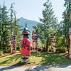 "These 6 totem figures are known as the ""Council of Clans.""  They are located near the main entrance to the Cape Fox Lodge in Kethchikan.               The figure wearing a red button blanket is holding a staff known as the Naa Kaani pole (not visible in this photo).  Speaking staffs were used at potlaches where the person holding it had the authority to mediate and bring order to the festivities.         <br /> <br /> Lee Wallace, the carver of these poles added a personal touch to the bear pole (the one in the center of the 5 facing the authority figure in the red button blanket).  According to him, the small bear cub on the top of the pole was for his daughter who loved ""Care Bears"" when she was little.  Although not visible in the photo, there is a small carved heart on the bear cub's behind!"