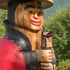 "This is one of the totems in the ""Council of Clans,"" a circle of 6 totem figures  located near the main entrance to the Cape Fox Lodge in Kethchikan.       The Council of Clans was created and carved by Lee Wallace.        This figure is known as the Naa Kaani pole.  He is wearing a traditional button blanket and holds a speaking staff.  Speaking staffs were used at potlaches where the person holding the staff had the authority to mediate and bring order to the festivities."