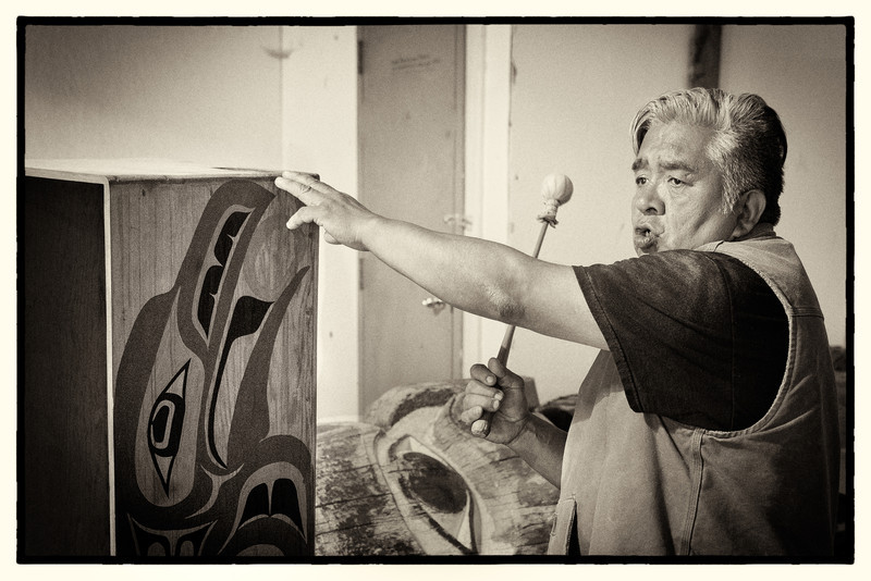 """Terry """"Hagoo"""" Peele is a proud Haida carver.  We met him at the carving shed in Hydaburg where he told us about Haida culture and sang for us.  He insisted that he is a Haida and doesn't like to be called an Indian, explaining that """"Columbus got that all wrong!""""  He is seen here singing a Haida song in the carving shed while accompanying himself on a bentwood box drum.         The Haida Gwaii Islands (formerly called the Queen Charlotte Islands) have been the ancestral home of the Haida for thousands of years but in the 17th century some of them emigrated (in dugout canoes) to Prince of Wales Island in Southeast Alaska and settled in a community now known as Hydaburg."""