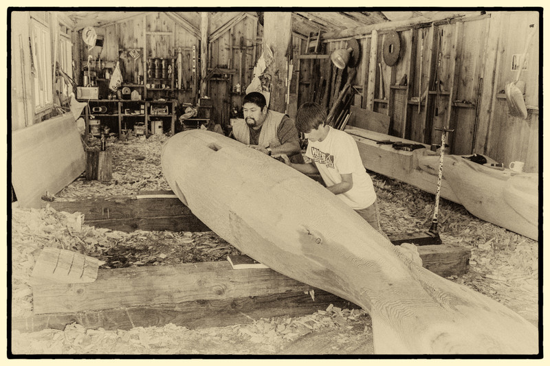 Jonathan O. Rowan, Jr. and his young apprentice in the carving shed in Klawock, AK.  They are rolling over a carved whale that will be mounted atop a pole to be erected at the Klawock schoolyard.  This pole is to be a replica of one that has deteriorated.  Carving is a required part of the Klawock school curriculum where Jonathan teaches carving.  This photo was taken by Albino Amador,