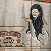 Carving by Brita Alander of a woman crouched next to a bentwood box.  Located  on the exterior of a longhouse at  Potlach Park near Ketchikan.