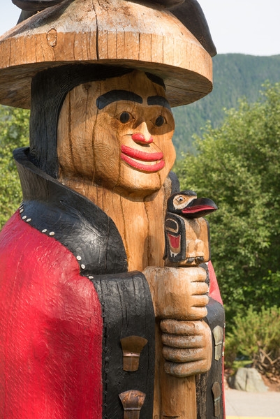 """This is one of the totems in the """"Council of Clans,"""" a circle of 6 totem figures  located near the main entrance to the Cape Fox Lodge in Kethchikan.       The Council of Clans was created and carved by Lee Wallace.        <br /> <br /> This figure is known as the Naa Kaani pole.  He is wearing a traditional button blanket and holds a speaking staff.  Speaking staffs were used at potlaches where the person holding the staff had the authority to mediate and bring order to the festivities."""