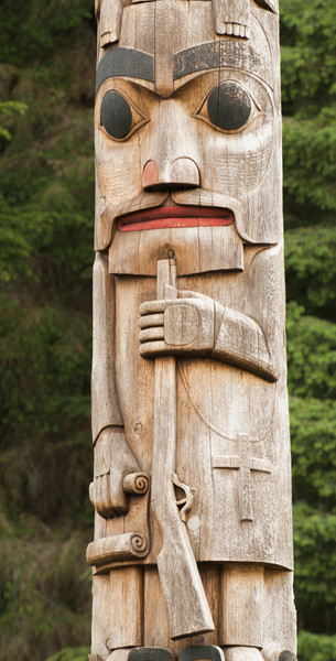 Detail of figure on pole by Duane Pasco at Sitka National Historical Park entrance.  This figure represents the arrival of white man bringing with him guns, Christianity, and a long line of treaties (see rolled documents in right hand.)  See 0706021-049 for more info on this pole.