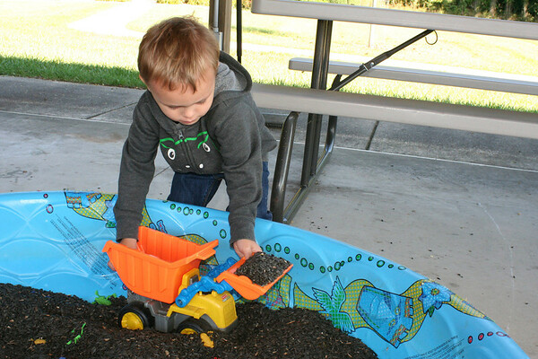 SHEILA SELMAN | THE GOSHEN NEWS<br /> Levi Sears, 3, Dunlap, enjoys picking up bird seed with a toy dump truck Saturday at Touch-A-Truck at Faith United Methodist Church, north of Goshen.