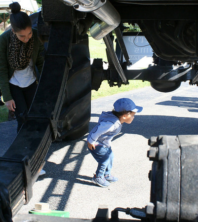 SHEILA SELMAN | THE GOSHEN NEWS<br /> John Deynes, 2, Mishawaka, checks underneath a monster truck owned by BAM! Tree Service. His mom, Kiona Deynes keeps an eye on him during Touch-A-Truck Saturday at Faith United Methodist Church, 22045 C.R. 18, Goshen.