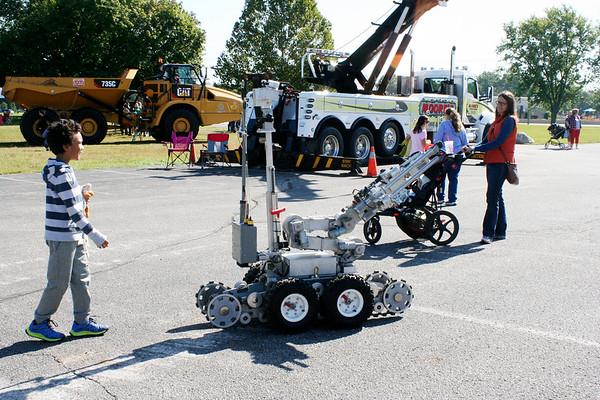 SHEILA SELMAN | THE GOSHEN NEWS<br /> Liam Okponobi, 7, Goshen, follows a robot around the parking lot at Faith United Methodist Church Saturday during Touch-A-Truck.