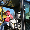 SHEILA SELMAN | THE GOSHEN NEWS<br /> Tiernan Owens, 6, Elkhart, enjoys sitting at the controls of a piece of excavation equipment Saturday during Touch-A-Truck at Faith United Methodist Church.