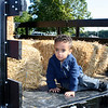 SHEILA SELMAN | THE GOSHEN NEWS<br /> Kai Herring, 2, Elkhart, isn't too sure about sitting in teh back of an antique pickup truck filled with straw bales at Touch-A-Truck.