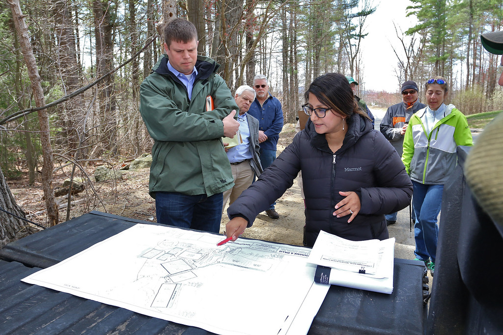 . Purvi Patel, an analyst with Massachusetts Environmental Policy Act (MEPA), asks questions of Greg Roy, the project engineer for the Game On site in Fitchburg, just before their tour of the land on Thursday morning April 20, 2017. Residents listen to them in the background as they wait for their turn to ask questions. SENTINEL & ENTERPRISE/JOHN LOVE