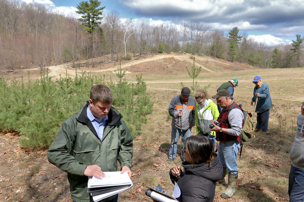 . Purvi Patel, an analyst with Massachusetts Environmental Policy Act (MEPA), asks questions of Greg Roy, the project engineer for the Game On site in Fitchburg, during their tour of the land on Thursday morning April 20, 2017. Residents look around in the background as the two discuss things. SENTINEL & ENTERPRISE/JOHN LOVE