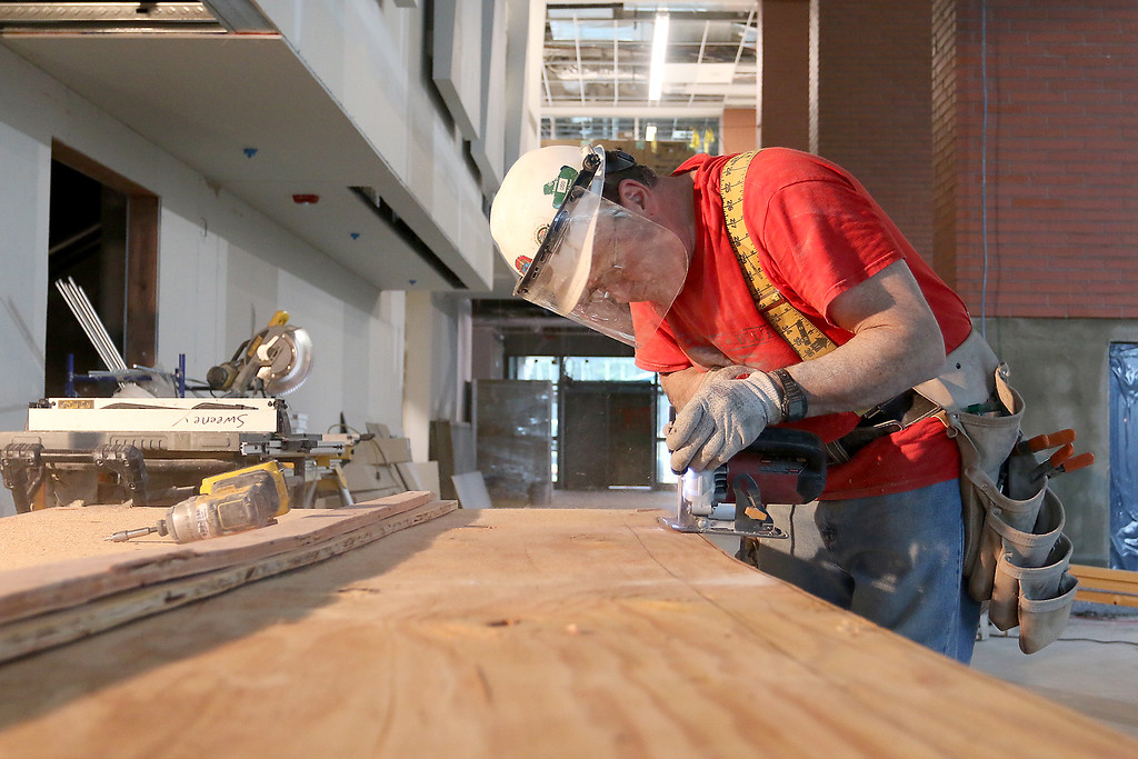 . Carpenter Rene Breton cuts some wood as he and others work on finishing the cafeteria at the new North Middlesex Regional High School in Townsend on April 12, 2017. SUN/JOHN LOVE