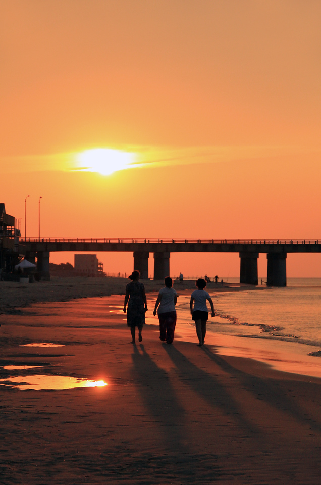 3 Friends walk in the sunset on Chick's Beach