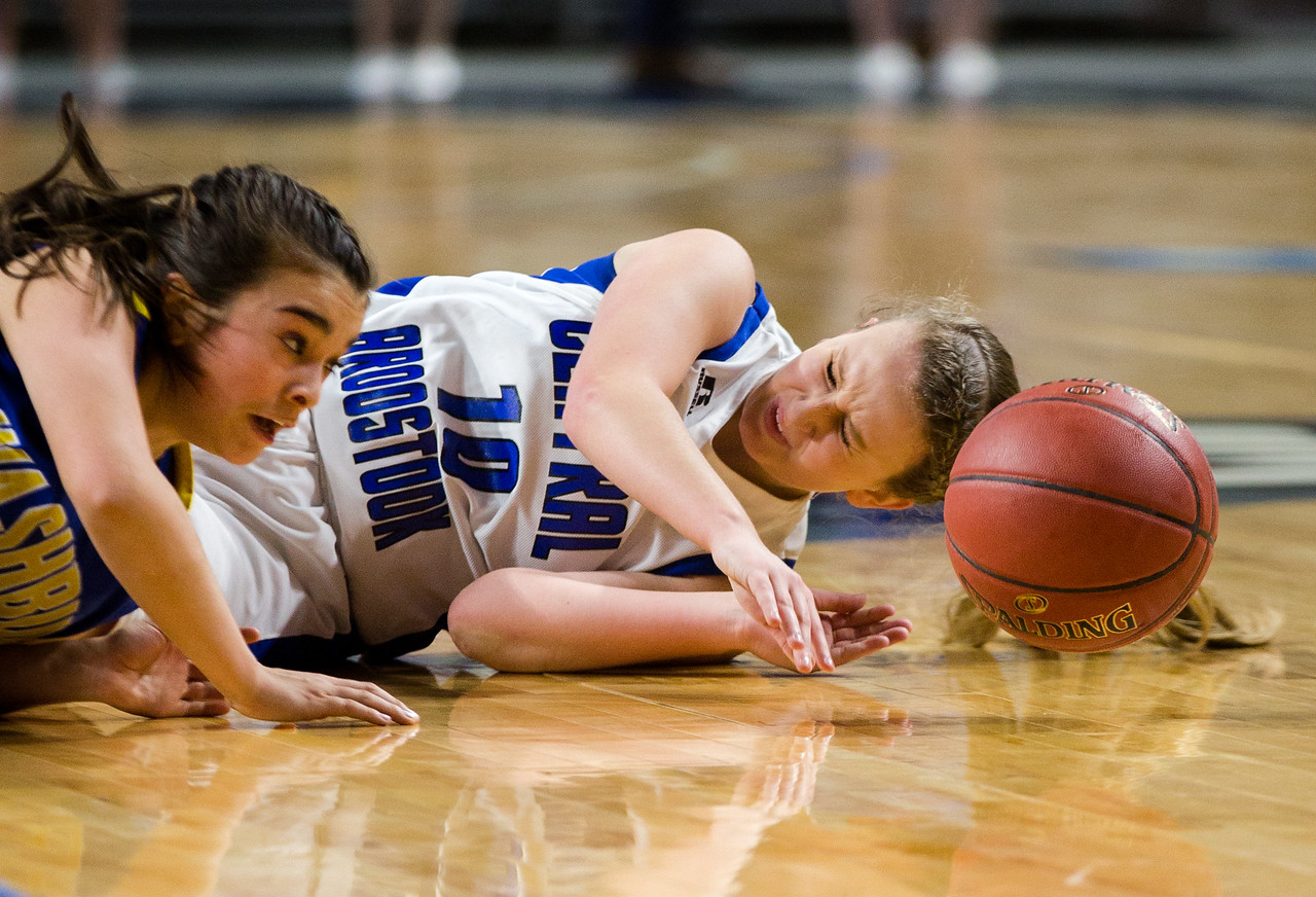 Central Aroostook's Kassidy Levesque and Washburn's Skylar Mette fall to the floor during pursuit of a loose ball during their game at the Cross Insurance Center in Bangor on Monday morning. Micky Bedell | BDN