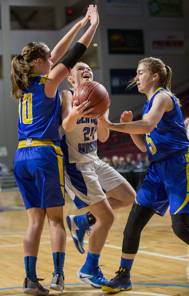 Central Aroostook's Ashlee Harris (center) pushes up against Washburn's Kassandra Farley (left) and Maggie Castonguay (right) to take a shot on basket during their game at the Cross Insurance Center in Bangor on Monday morning. Micky Bedell | BDN