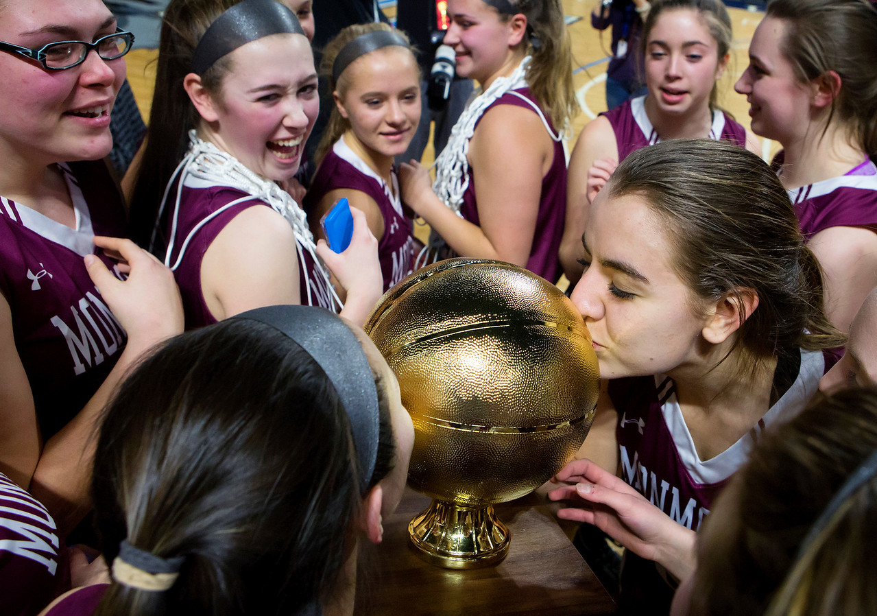 BANGOR, Maine -- 03/04/2017 -- Monmouth players kiss the golden ball after defeating Dexter during their Class C girls basketball state championship at the Cross Insurance Center in Bangor Saturday. Ashley L. Conti | BDN