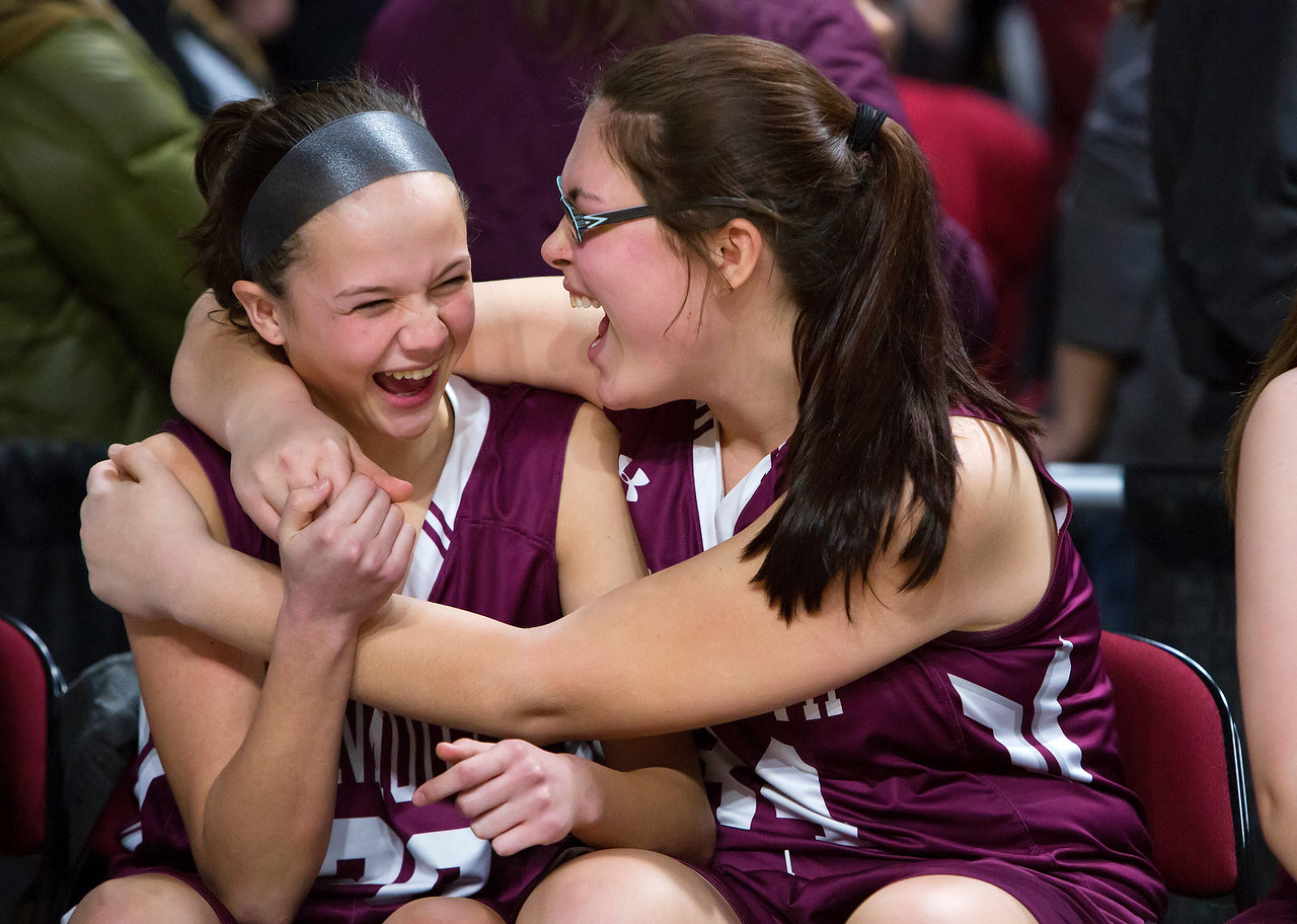 BANGOR, Maine -- 03/04/2017 -- Monmouth's Libby A. Clement (left) embraces Monmouth's Destiny Clough after defeating Dexter during their Class C girls basketball state championship at the Cross Insurance Center in Bangor Saturday. Ashley L. Conti | BDN