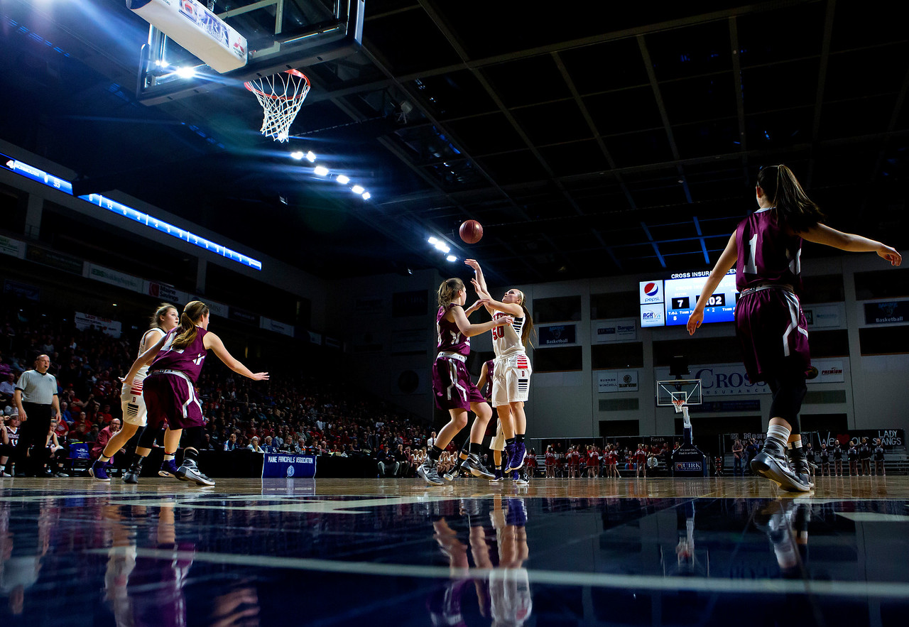 BANGOR, Maine -- 03/04/2017 -- Dexter's Kayli Cunningham (center) tries for two past Monmouth's Madalyn Amero during their Class C girls basketball state championship at the Cross Insurance Center in Bangor Saturday. Ashley L. Conti | BDN
