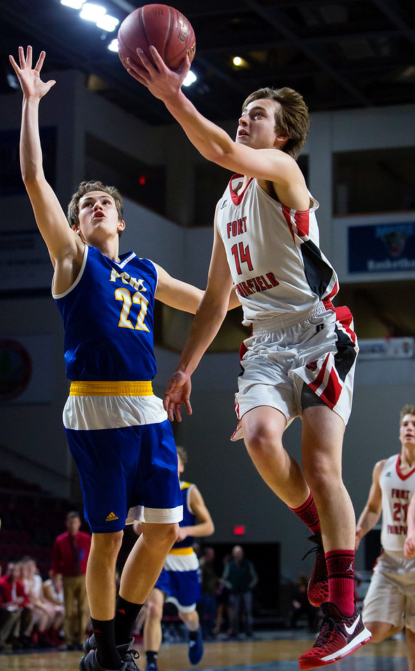 BANGOR, Maine -- 02/21/2017 -- Fort Fairfield's Christopher Giberson (right) floats a shot in past Piscataquis' Bryce Gilbert during their Class C boys basketball quarterfinal game at the Cross Insurance Center in Bangor Tuesday. Ashley L. Conti | BDN