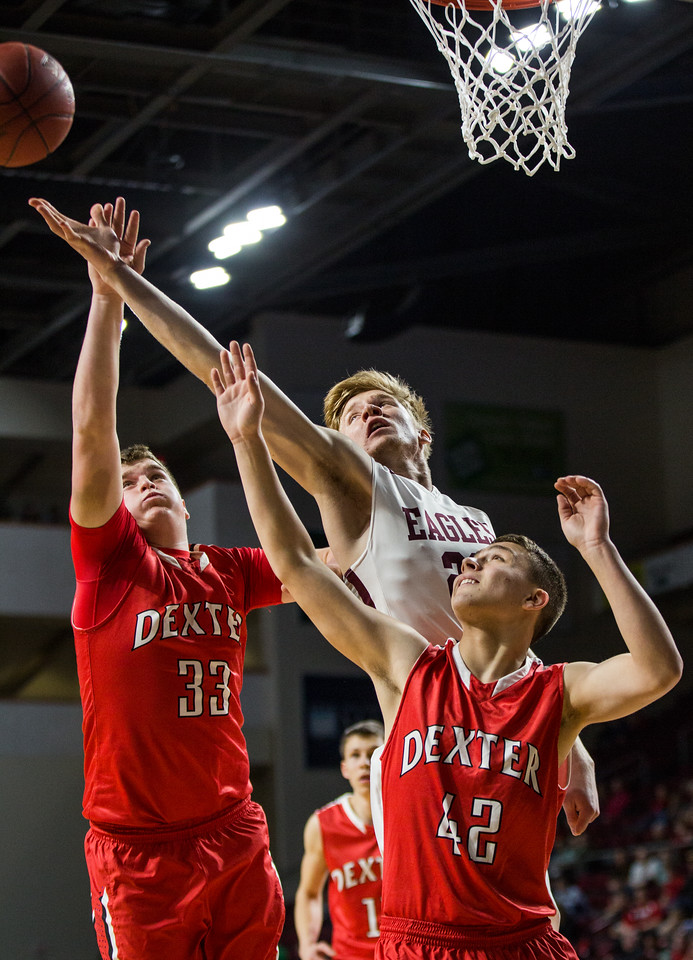 BANGOR, MAINE -- 02/24/2017 -- George Stevens Academy's Maxwell Mattson (center) reaches out for a rebound, blocked by Dexter's Brayden Miller (left) and Jacob Bickford during their class C boys semifinal game at the Cross Insurance Center on Friday evening. Micky Bedell | BDN