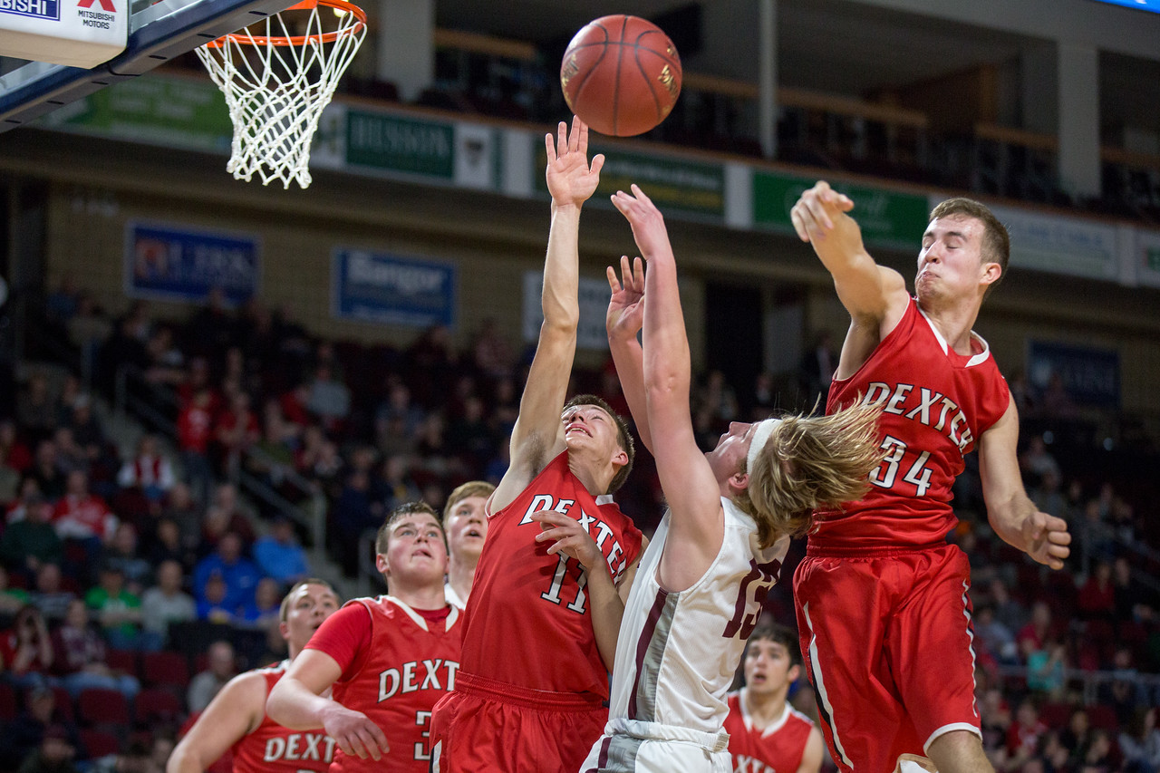 BANGOR, MAINE -- 02/24/2017 --  Dexter's Zachary White (far right) whips the ball out of bounds from a rebound as George Stevens Academy's Beckett Slayton (center right) and teammate William Strauch (center left) reach for it during their class C boys semifinal game at the Cross Insurance Center on Friday evening. Micky Bedell   BDN