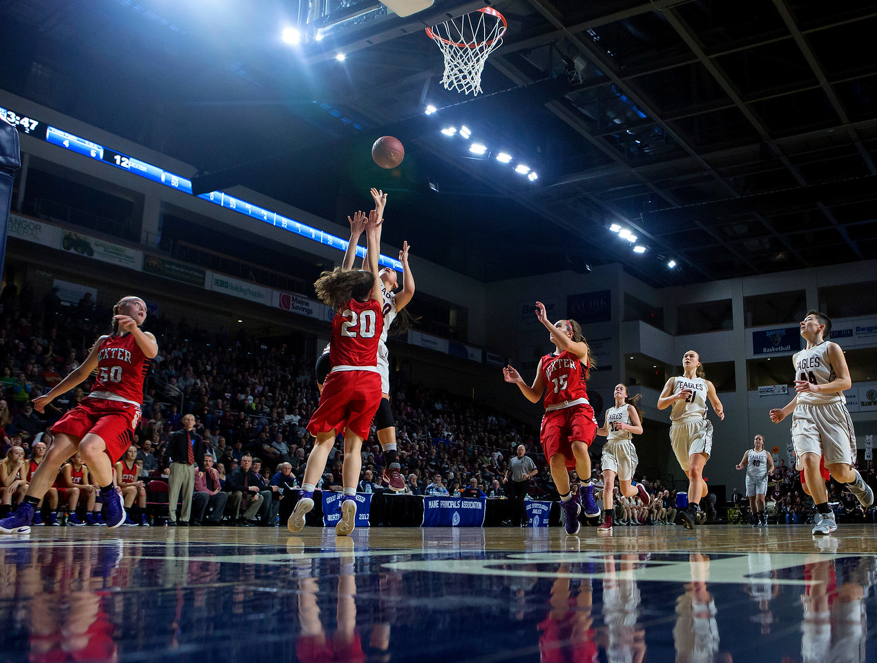 BANGOR, Maine -- 02/25/2017 -- George Stevens Academy's Julianna Allen (center) leaps up for two past Dexter's Ashley Reynolds during their Class C girls basketball championship game at the Cross Insurance Center in Bangor Saturday. Ashley L. Conti   BDN