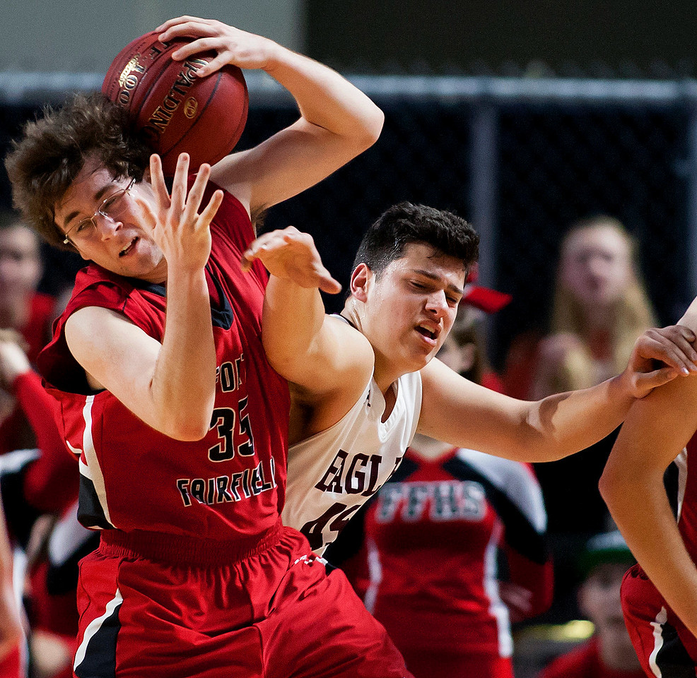 BANGOR, Maine -- 02/25/2017 -- Fort Fairfield's Carter Bruce (left) tries to gain control of a loose ball against George Stevens Academy's Stefan Simmons during their Class C boys basketball championship game at the Cross Insurance Center in Bangor Saturday. Ashley L. Conti | BDN
