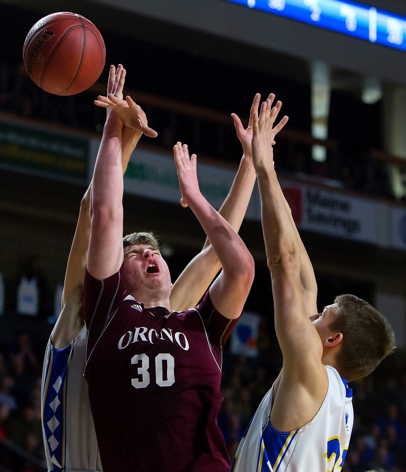 BANGOR, Maine -- 02/22/2017 -- Orono's Connor Robertson (center) is fouled by Hermon's Isaac Varney (left) during their Class B boys basketball semifinal game at the Cross Insurance Center in Bangor Wednesday. Ashley L. Conti | BDN