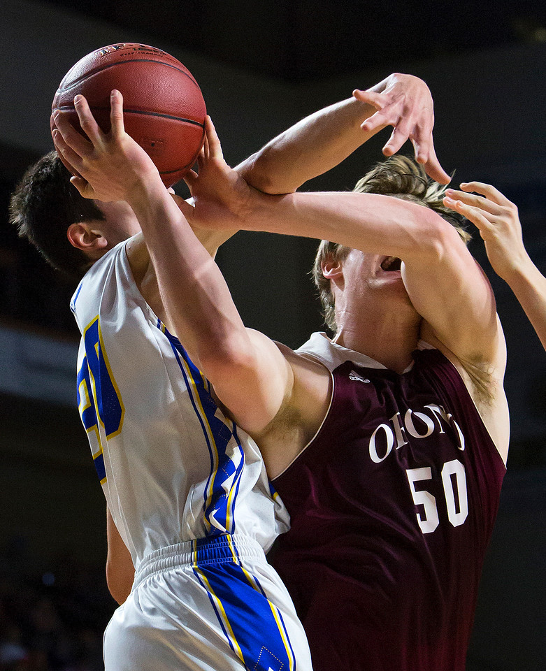 BANGOR, Maine -- 02/22/2017 -- Hermon's Isaac Varney (left) fouls Orono's Keenan Collett during their Class B boys basketball semifinal game at the Cross Insurance Center in Bangor Wednesday. Ashley L. Conti | BDN