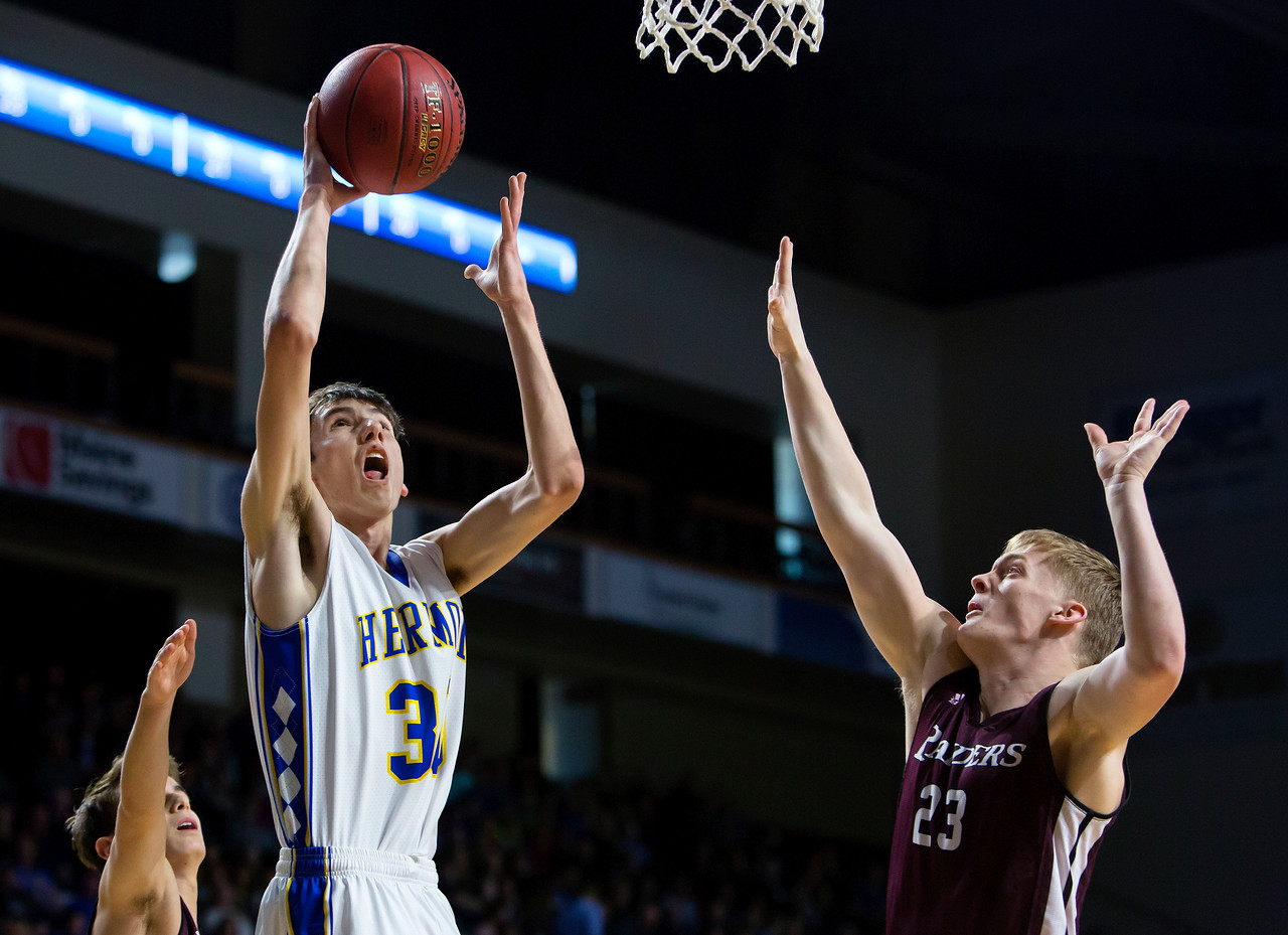 BANGOR, Maine -- 02/18/2017 -- Hermon's Isaac Varney (center) drives up for two past Washington Academy's Justin M. Vilone during their Class B boys basketball quarterfinal game at the Cross Insurance Center in Bangor Saturday. Ashley L. Conti | BDN