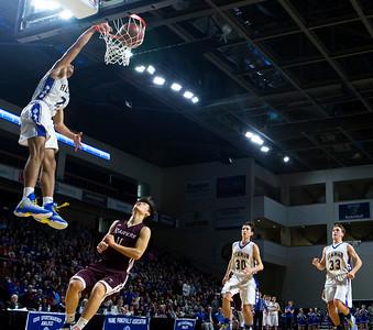 BANGOR, Maine -- 02/18/2017 -- Hermon's Keenan Marseille sinks a dunk past Washington Academy's Ching Jim Lin during their Class B boys basketball quarterfinal game at the Cross Insurance Center in Bangor Saturday. Ashley L. Conti | BDN