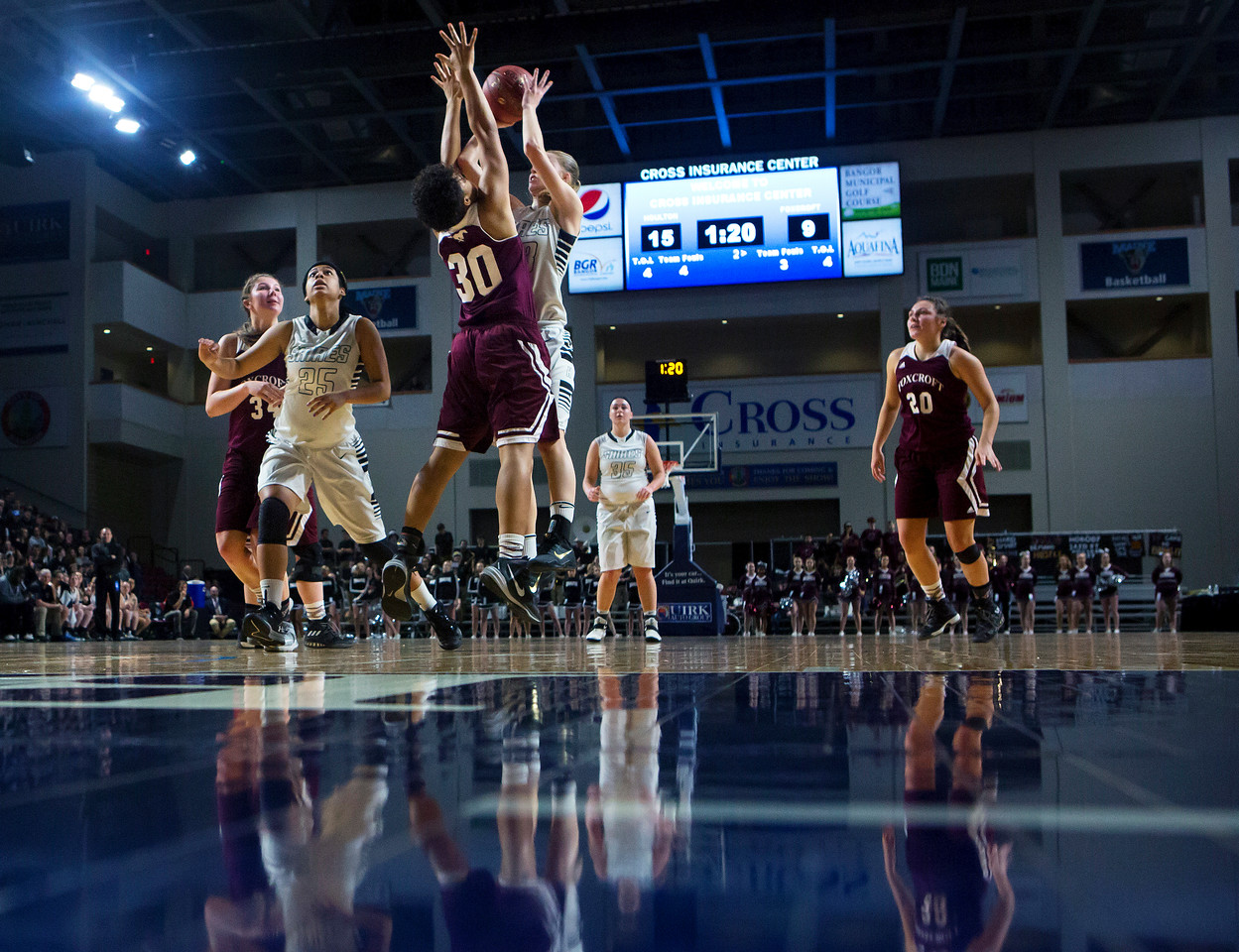 BANGOR, Maine -- 02/25/2017 -- Houlton's Kolleen Bouchard (center) puts up a shot with strong defense from Foxcroft Academy's Emily Mikoud during their Class B girls basketball championship game at the Cross Insurance Center in Bangor Saturday. Ashley L. Conti   BDN