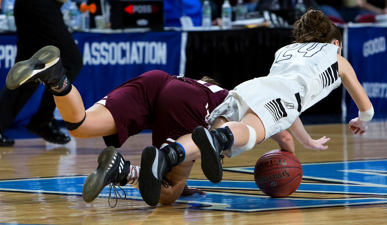 BANGOR, Maine -- 02/25/2017 -- Foxcroft Academy's Kendra Ewer (left) and Houlton's Rylee Warman leap through the air to try to win a loose ball during their Class B girls basketball championship game at the Cross Insurance Center in Bangor Saturday. Ashley L. Conti | BDN