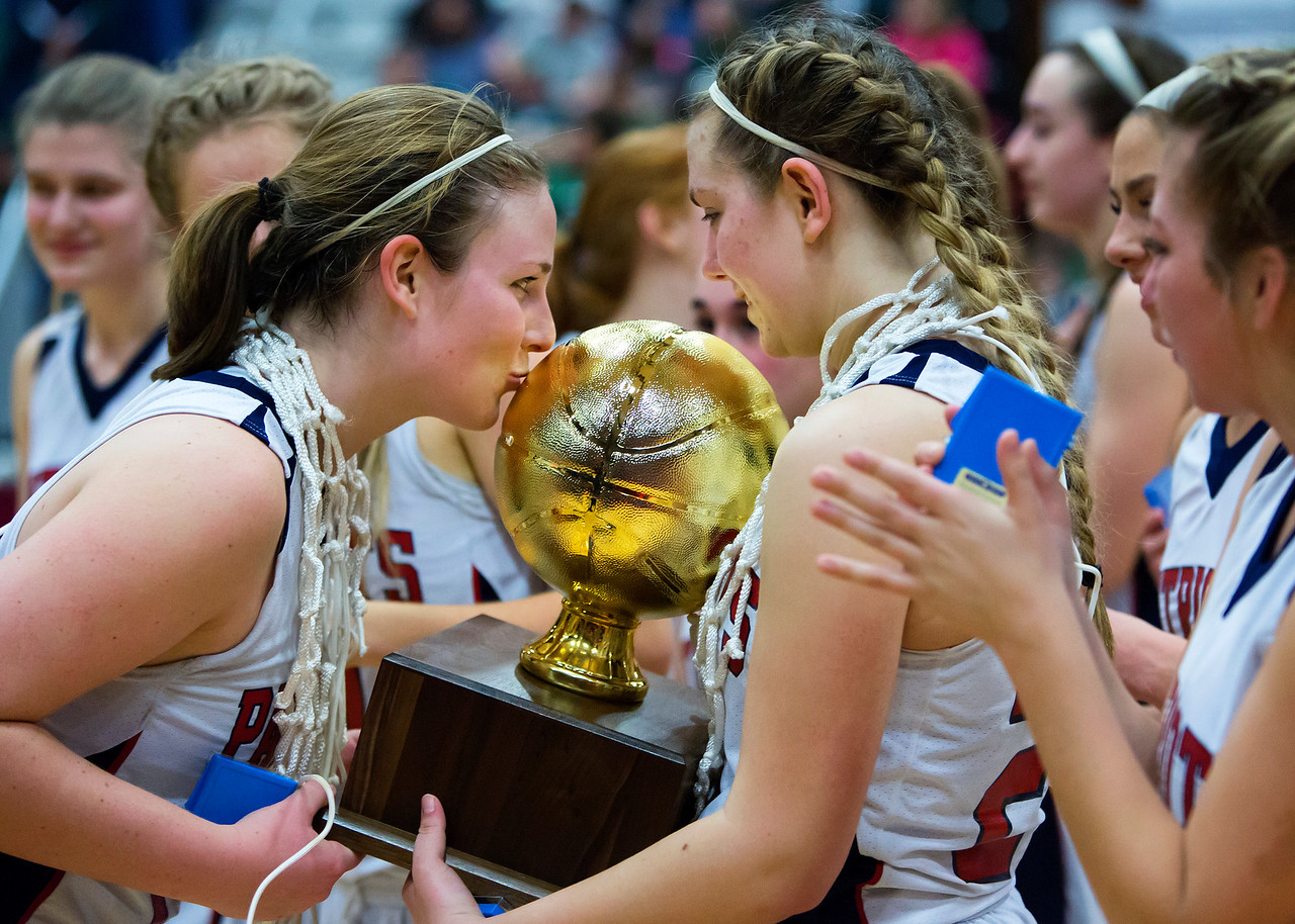 AUGUSTA, Maine -- 03/03/2017 -- Gray-New Gloucester's Skye Conley (left) gives the state championship trophy a kiss after defeating Houlton during their Class B girls basketball state championship at the Augusta Civic Center in Augusta Friday. Ashley L. Conti | BDN