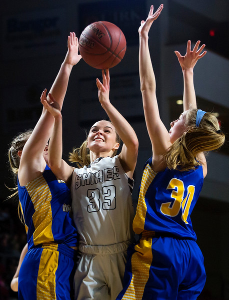 BANGOR, Maine -- 02/22/2017 -- Houlton's Kristen Brewer (center) is fouled by Hermon's Lauren Plissey (right) during their Class B girls basketball semifinal game at the Cross Insurance Center in Bangor Wednesday. Ashley L. Conti | BDN