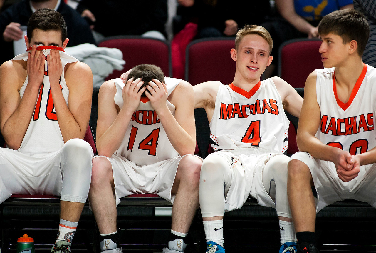 BANGOR, Maine -- 03/04/2017 -- Machias' John Massaad (from left), Machias' Jordan Grant, Machias' Russell Hanscom, and Machias' Alessandro Marotta sit in disbelief after defeating Greenville during their Class D boys basketball state championship at the Cross Insurance Center in Bangor Saturday. Ashley L. Conti | BDN
