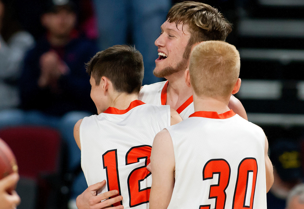 BANGOR, Maine -- 03/04/2017 -- Machias' Camon Johnson (left) celebrates with Machias' James Mersereau (center) and Machias' Noah Albert after defeating Greenville during their Class D boys basketball state championship at the Cross Insurance Center in Bangor Saturday. Ashley L. Conti | BDN