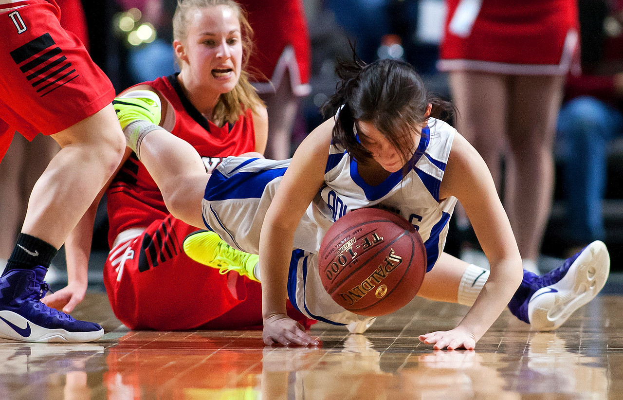 BANGOR, Maine -- 02/21/2017 -- Madawaska's Desiree Belanger (right) gets tripped up by Dexter's Abigail Webber during their Class C girls basketball quarterfinal game at the Cross Insurance Center in Bangor Tuesday. Ashley L. Conti   BDN