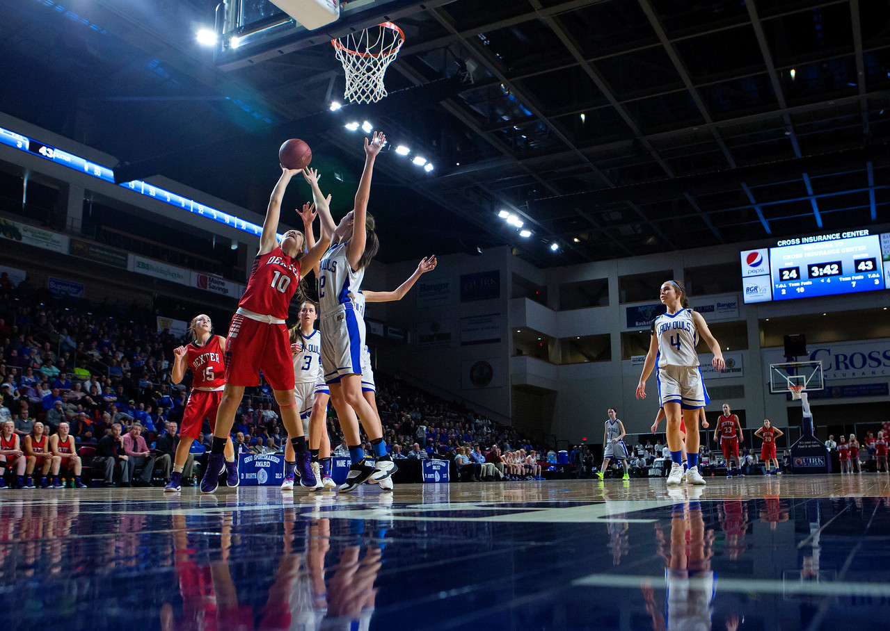 BANGOR, Maine -- 02/21/2017 -- Dexter's Rebecca Batron (left) goes up for two past Madawaska's Jenna Dugal during their Class C girls basketball quarterfinal game at the Cross Insurance Center in Bangor Tuesday. Ashley L. Conti | BDN