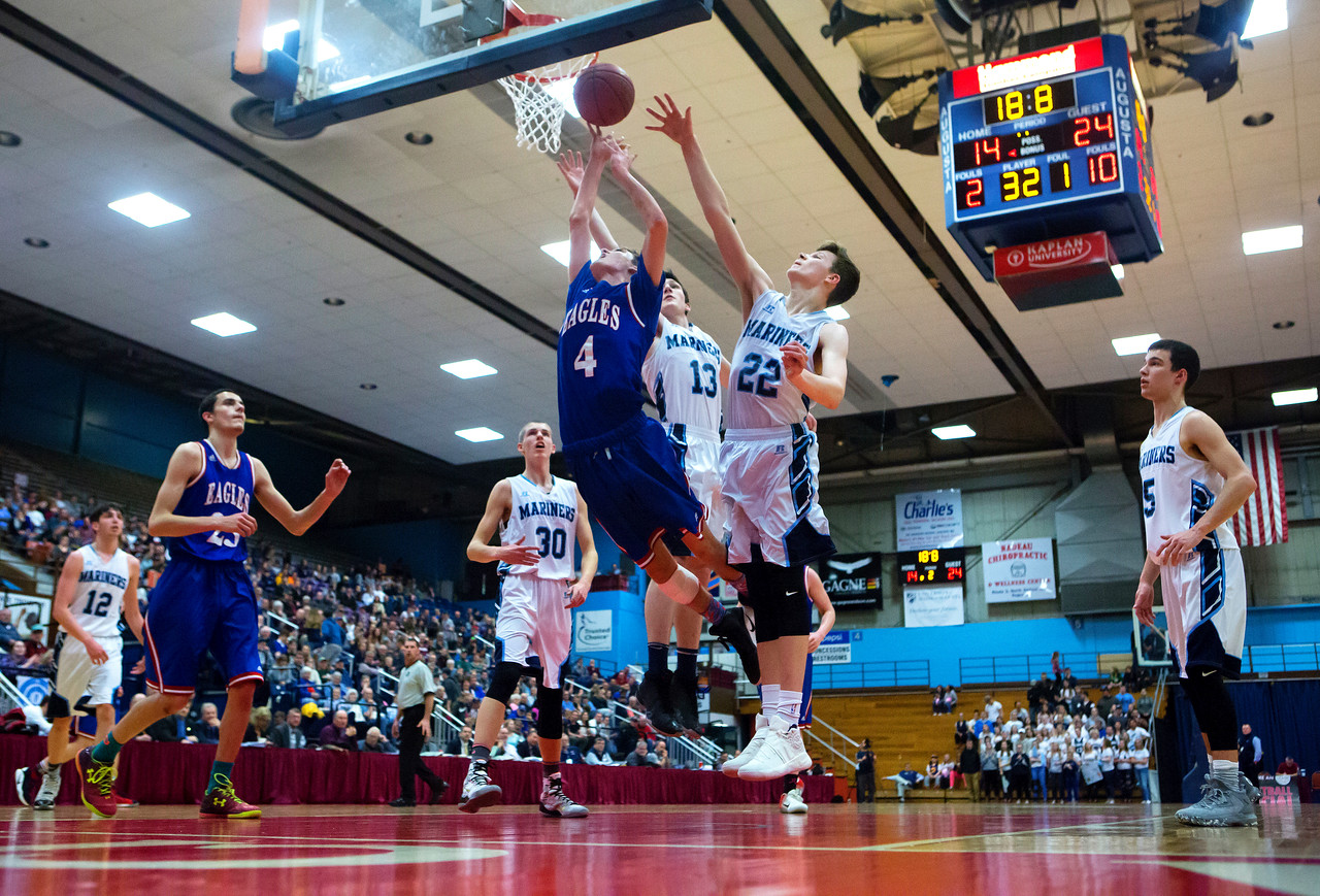 AUGUSTA, Maine -- 02/24/2017 -- Messalonskee's James Kouletsis (center) tries for two past Oceanside's Cooper Wirkala (right) and Oceanside's Michael Norton, Jr. during their Class A boys basketball championship game at the Augusta Civic Center in Augusta Friday. Ashley L. Conti | BDN