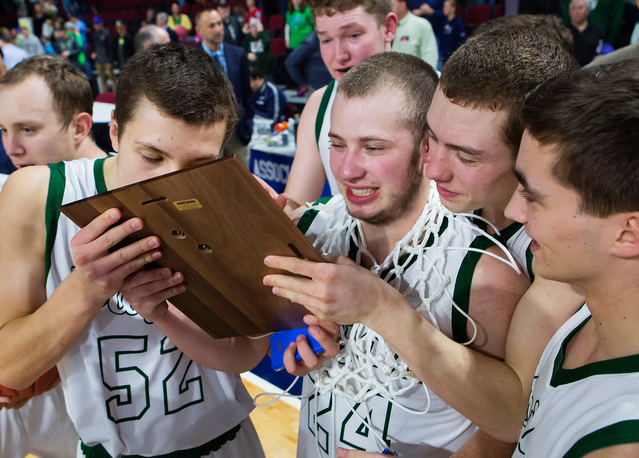 BANGOR, Maine -- 02/25/2017 -- Mount Desert Island's Derek Collin gives the first place plaque a kiss after defeating Orono during their Class B boys basketball championship game at the Cross Insurance Center in Bangor Saturday. Ashley L. Conti | BDN