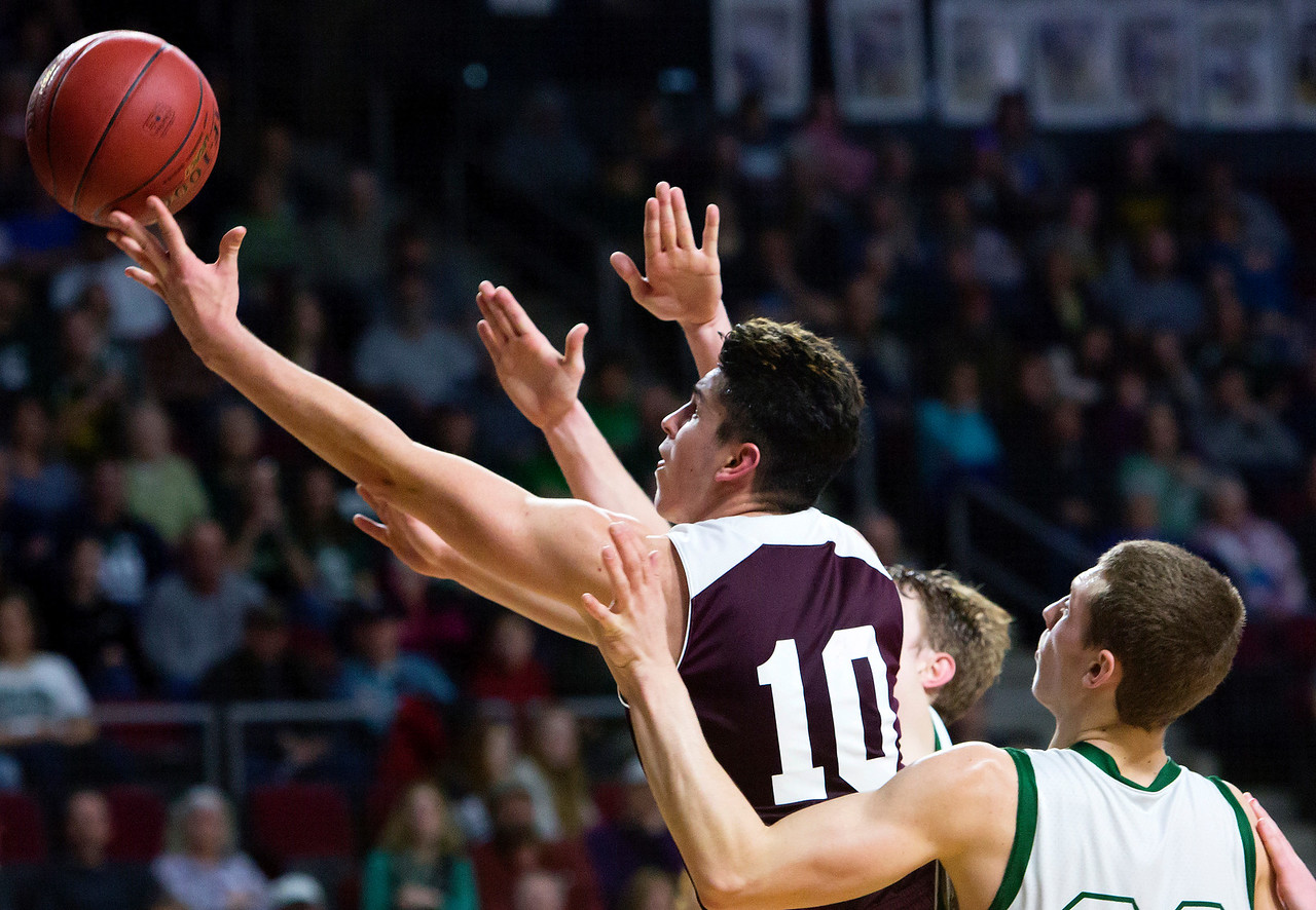 BANGOR, Maine -- 02/25/2017 -- Orono's Nate Desisto (left) tries for two past Mount Desert Island's Graham Good during their Class B boys basketball championship game at the Cross Insurance Center in Bangor Saturday. Ashley L. Conti | BDN